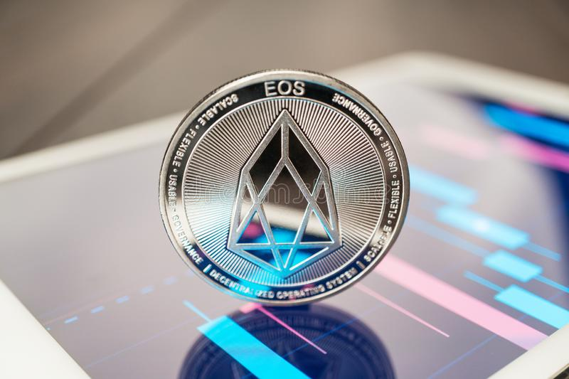 Close-up photo of eos cryptocurrency physical coin on the tablet computer showing stock market charts. trading eos cryptocoin. Concept on the wooden table royalty free stock photos