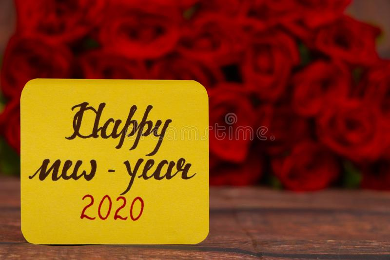 Happy New Year 2020 text with Red roses in a bunch as a background. Happy New Year 2020 concept royalty free stock photography