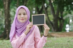Pretty young excited woman holding empty blank chalkboard for text. Royalty Free Stock Photography