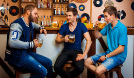Three men talking and drinking beer in bar Royalty Free Stock Photos