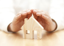 Wooden toy house protected by hands Stock Photo